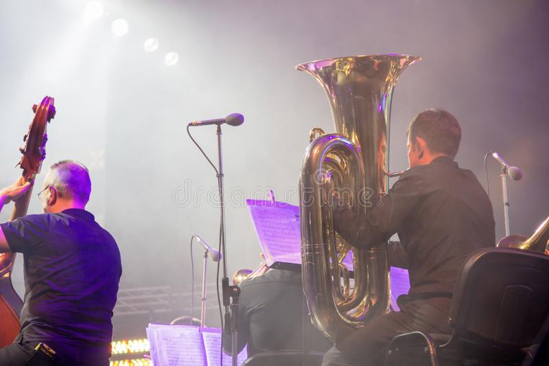 Symfoniorkestern på etappen, orkester- mässingsavsnitt, bak platserna skjuter fotografering för bildbyråer
