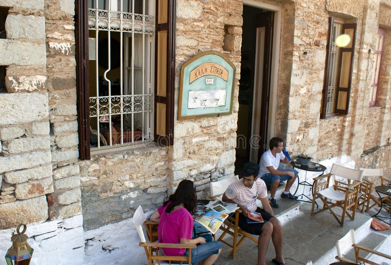 Symi / Greece / August 14 2009 : A cafe in the upper town.  Relaxed tourists enjoy a drink in a bar in a converted old fashioned royalty free stock photo