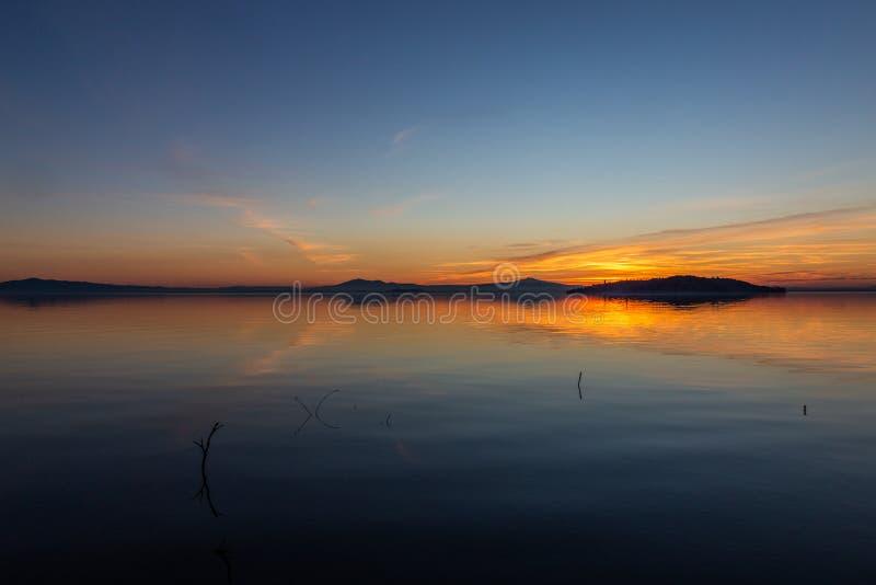 Symmetrcal, belle vue de lac Ombrie, Italie Trasimeno au coucher du soleil, avec des tons oranges et bleus dans le ciel photo stock