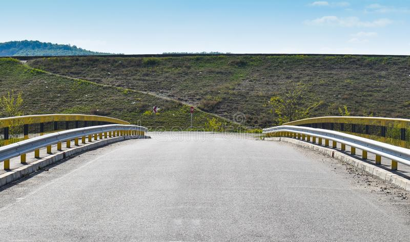 Symmetric picture along the empty bridge on the asphalt road stock photography