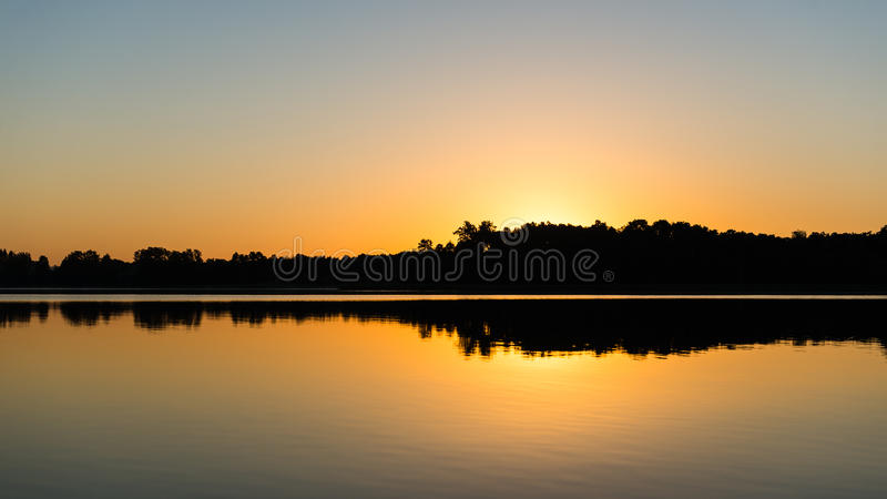 Symmetric reflections on calm lake. Water with forests and islands royalty free stock image