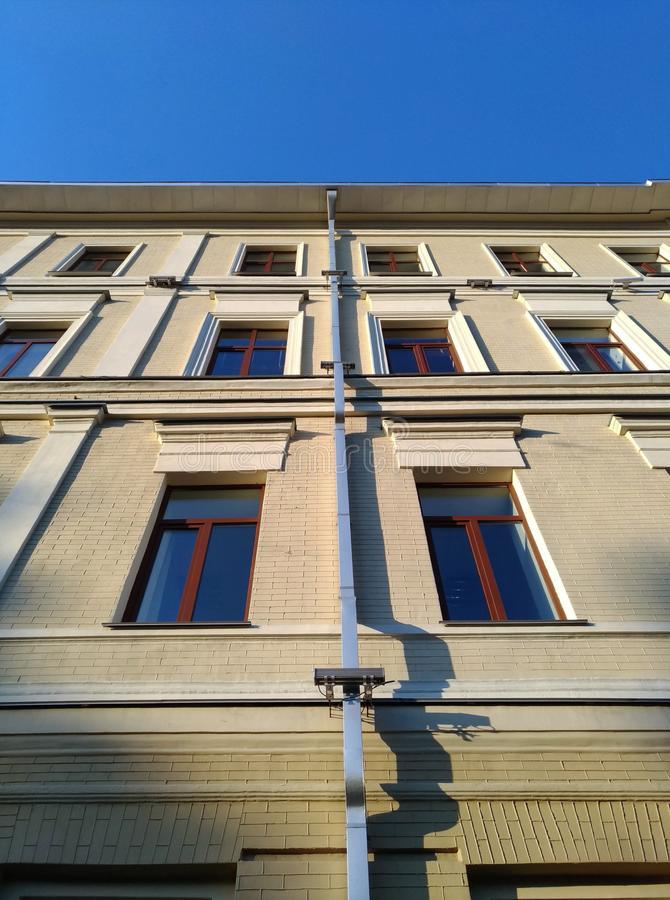 Symmetrical composition, wall, building, drainpipe. Symmetrical composition with the wall of building with a drainpipe and a strip of blue sky. Minimalistic royalty free stock photos