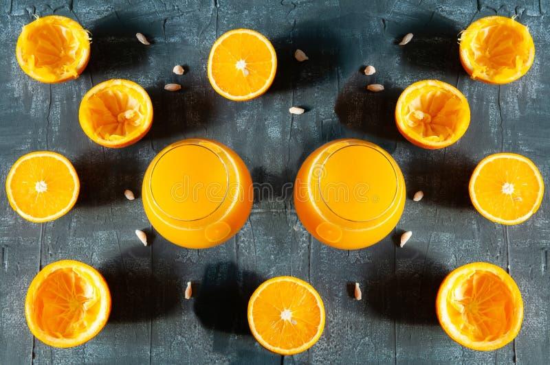Symmetrically placerade konjakexponeringsglas med ny orange fruktsaft Bredvid exponeringsglaset ?r skivade apelsiner och m?rk bak fotografering för bildbyråer