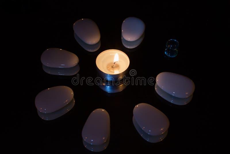 Symmetrische Steinblume durch Kerzenlicht lizenzfreie stockfotografie
