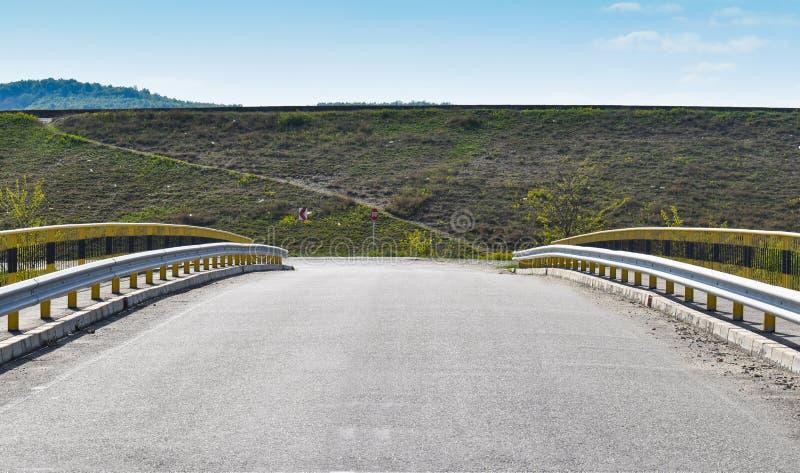 Symmetrisk bild längs den tomma bron på asfaltvägen arkivbild