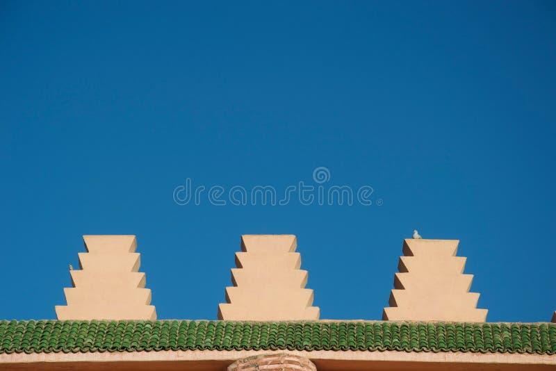 Symmetrisk detalj av marockansk arkitektur mot himlen, med en duva royaltyfria bilder
