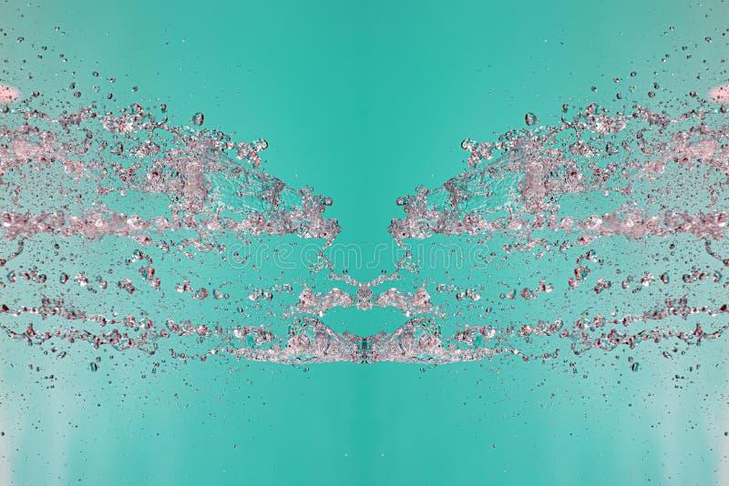 Symmetrisk modell av stoppade vattensmå droppar med genomskinliga strömmar på en grön bakgrund Sammandrabbning, opposition och my fotografering för bildbyråer