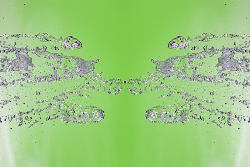 Symmetrisk modell av stoppade vattensmå droppar med genomskinliga strömmar på en grön bakgrund Sammandrabbning, opposition och my royaltyfria foton