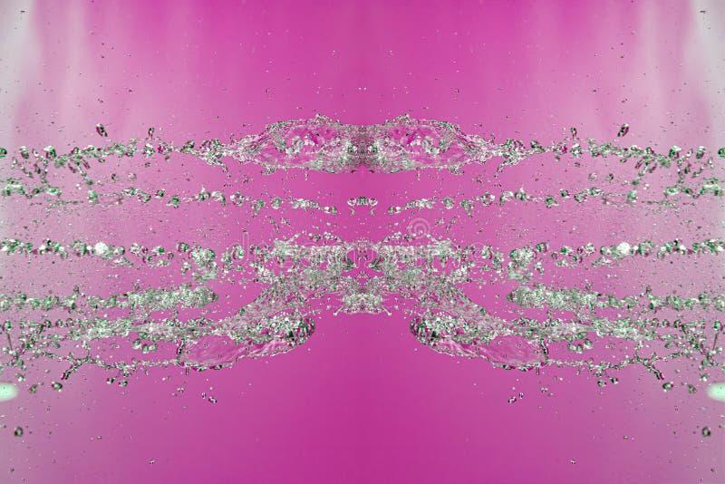 Symmetrisk modell av stoppade vattensmå droppar med genomskinliga strömmar på en rosa bakgrund Sammandrabbning, opposition och my royaltyfri foto