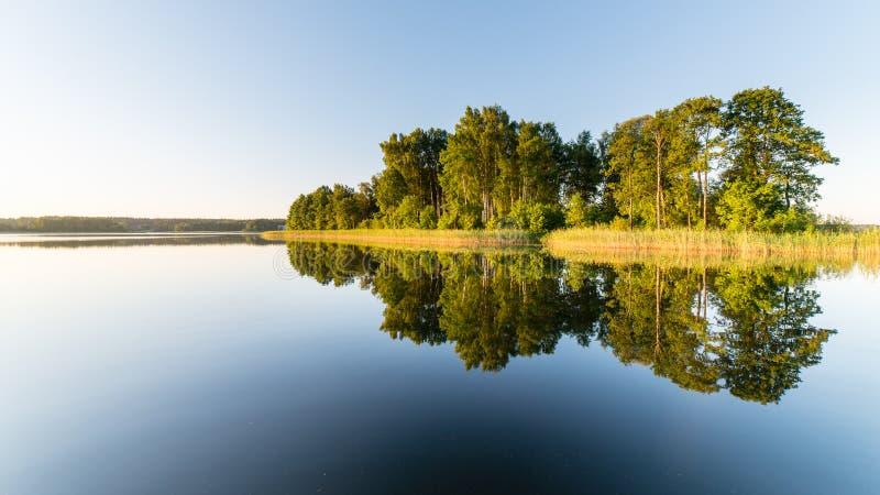 Symmetriska reflexioner på den lugna sjön arkivbild