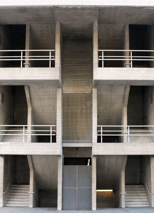 Symmetriska vinkelformiga brutalistbetongtrappor med multipelgolv och räcke i en stor modern byggnad royaltyfria foton