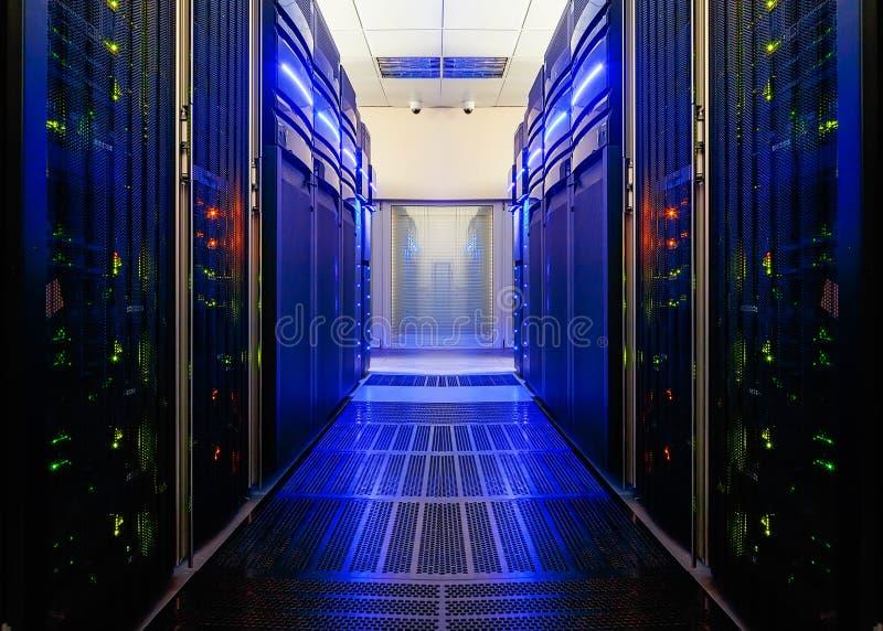 Symmetriskt datorhallrum med futuristiska strålar och rader av utrustning fotografering för bildbyråer
