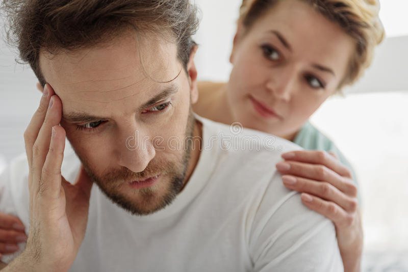 Sympathetic woman supporting her husband in difficult situation. Portrait of upset men has troubles at work. His wife is trying to calm him down while looking at stock photography