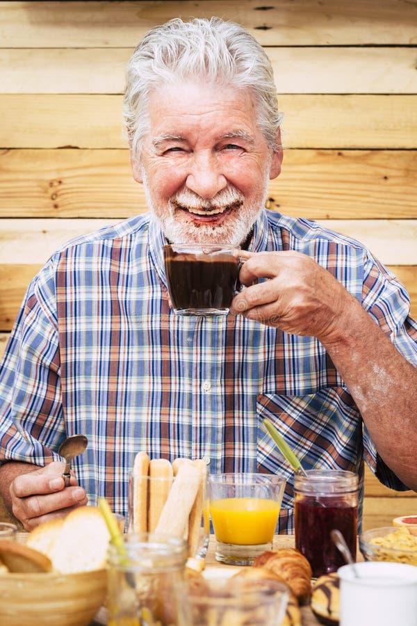 Sympathique et amusant homme d'âge actif et joyeux buvant du chocolat chaud avec barbe et moustache sale - heureux retraités appr photographie stock
