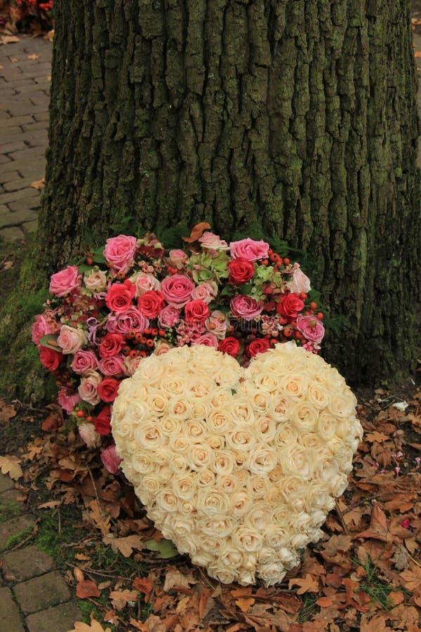 Sympathy flowers near a tree. Sympathy or funeral flowers near a tree royalty free stock photo