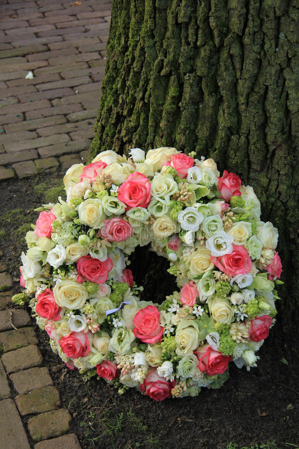 Sympathy wreath near tree. Sympathy wreath near a tree, pink and white roses royalty free stock images
