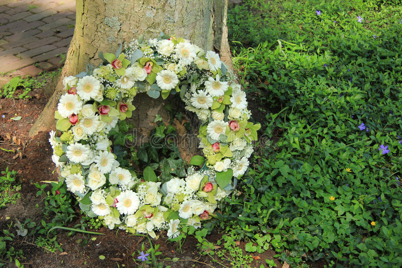 Sympathy wreath. Near a tree, various sorts of white flowers royalty free stock images