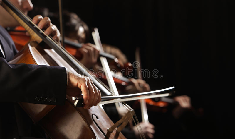 Symphony concert. A man playing the cello, hand close up stock image