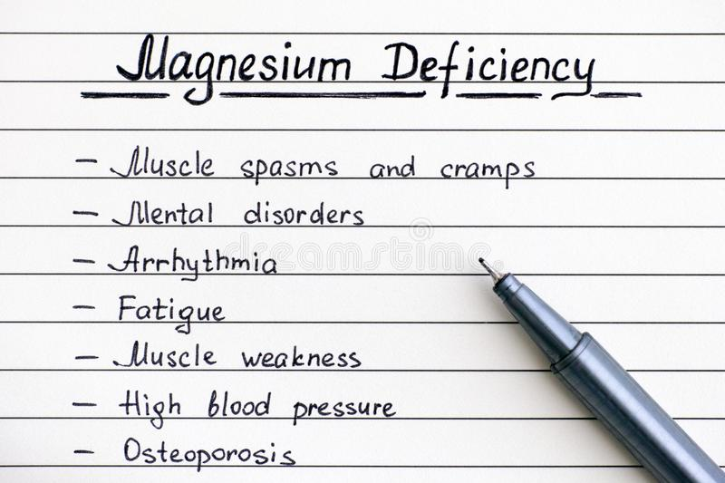 Symptoms of Magnesium Deficiency writing on the list with pen. Close-up stock photo