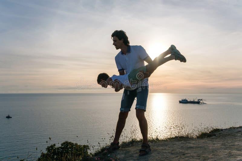 Syn na tata ` s rękach na górze z nadmorski Bawić się wpólnie przy zmierzchem Zabawy rozrywka zdjęcie royalty free