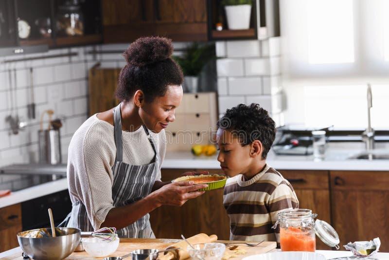 Syn pomaga matce w przygotowaniu ciasta dyniowego fotografia royalty free