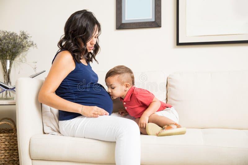 Syna całowania Mum ` s Ciężarny brzuch W Domu obraz stock