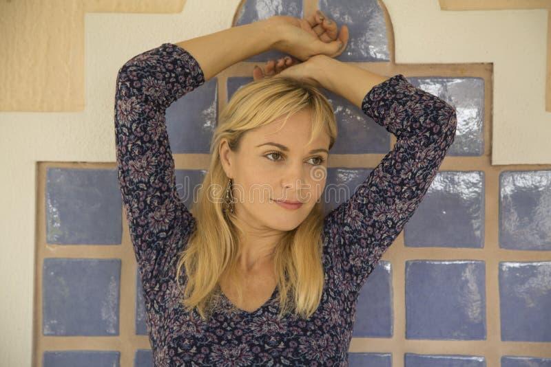 Synad modell för blont hår brunt med henne armar upp mot tegelplattabakgrund royaltyfria bilder