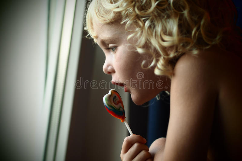 Synade blonda blått behandla som ett barn flickan med en godis i hennes hand som ut ser fönstret arkivfoto
