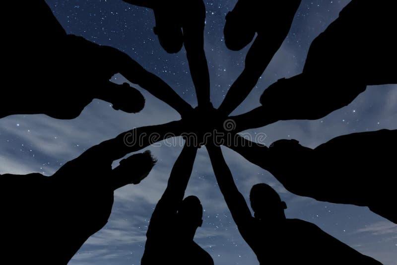 synergie Le travail d'équipe joignent le concept de soutien de mains ensemble Ciel de nuit photographie stock libre de droits