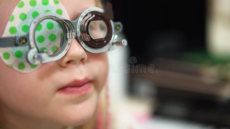 Synförmågakontroll Caucasian flicka som har visionhandikapp Medicinsk behandling och rehabilitering fotografering för bildbyråer