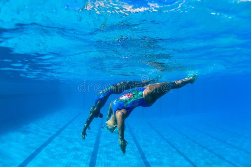 Synkroniseringssimma undervattens- fotodans för flickor arkivfoton