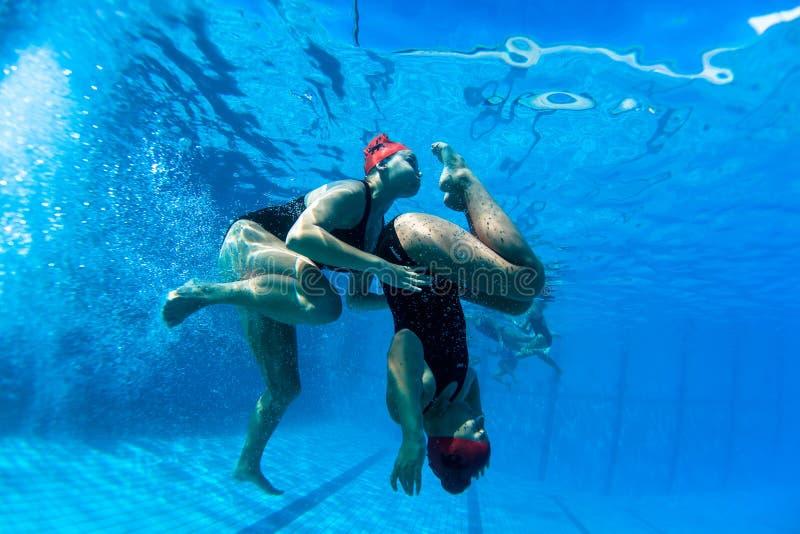 Synkroniseringssimma undervattens- fotodans för flickor royaltyfri foto