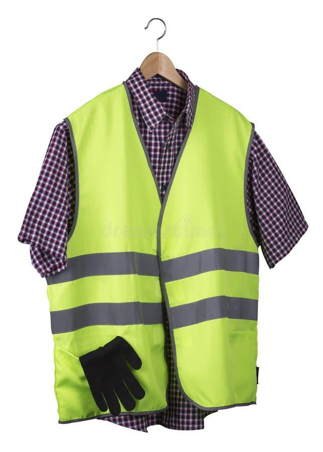 Synlighetsväst och skjorta på en trähängare arkivbild