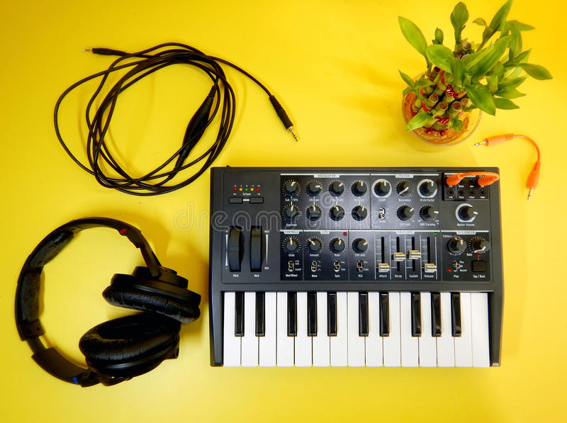 Synthesizer op gele achtergrond met oranje flardkabels en hoofdtelefoons royalty-vrije stock foto