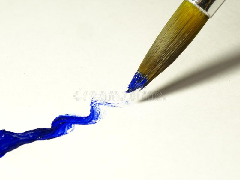 Wet brush with blue paint close-up. royalty free stock photos