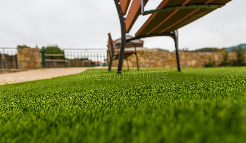 Synthetic Grass On a Park With Benches on a Pale Sky. Synthetic Grass On a Park With Benches on a Pale Blue Sky royalty free stock photography