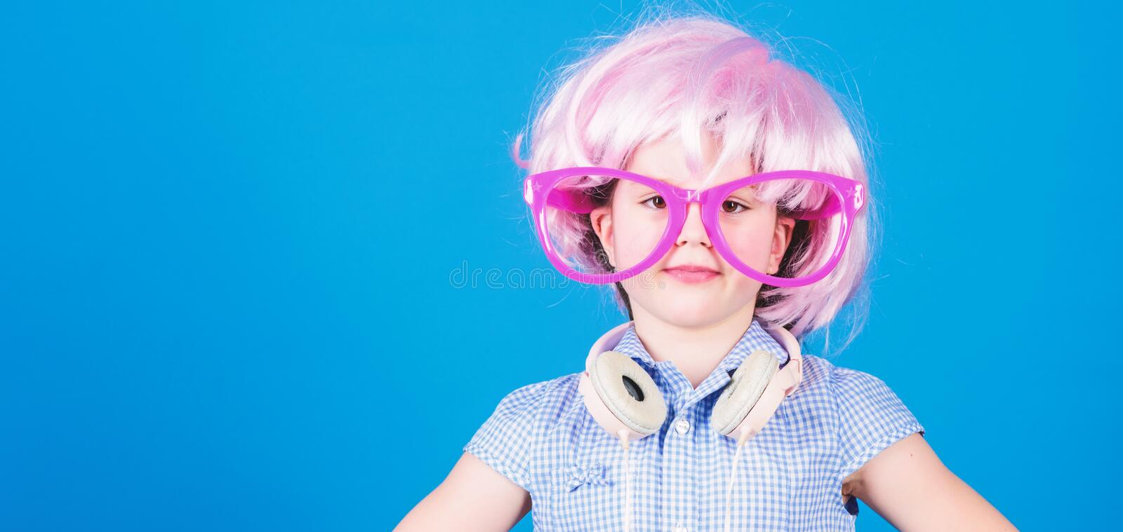 Synthetic hair. Cool little child with pink hair wig. Adorable small girl with fancy hair style wearing headphones stock photography