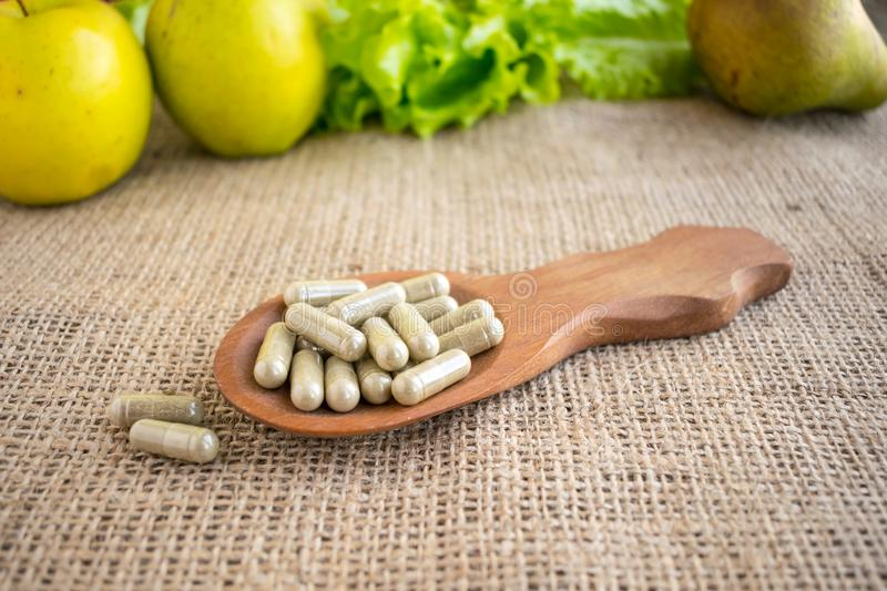 Synthetic or Natural Vitamins. Veggie capsules in brown wooden s royalty free stock photography