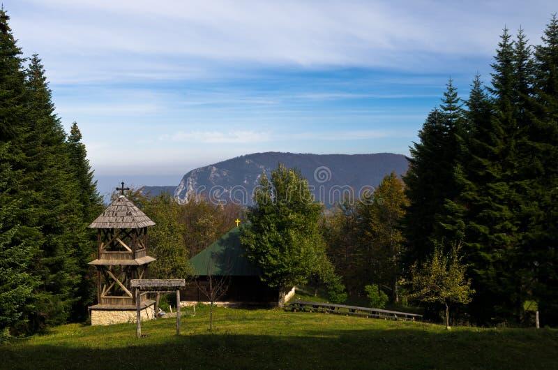 Synvinkel på ett landskap av monteringen Bobija, äng framme av en gammal träkyrka som omges av högväxta granträd royaltyfri fotografi