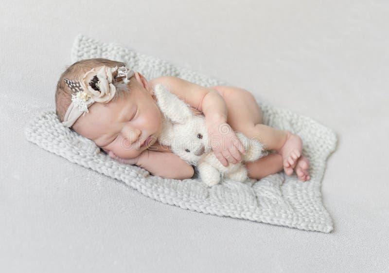Sypialna dziewczynka z zabawką na trykotowej koc fotografia royalty free