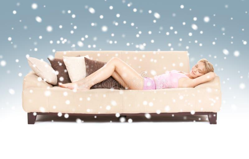 Sypialna kobieta na kanapie z śniegiem zdjęcie stock
