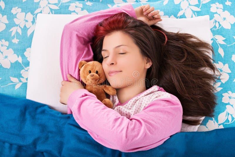 Sypialna młoda dziewczyna ściska jej niedźwiedzia obrazy royalty free