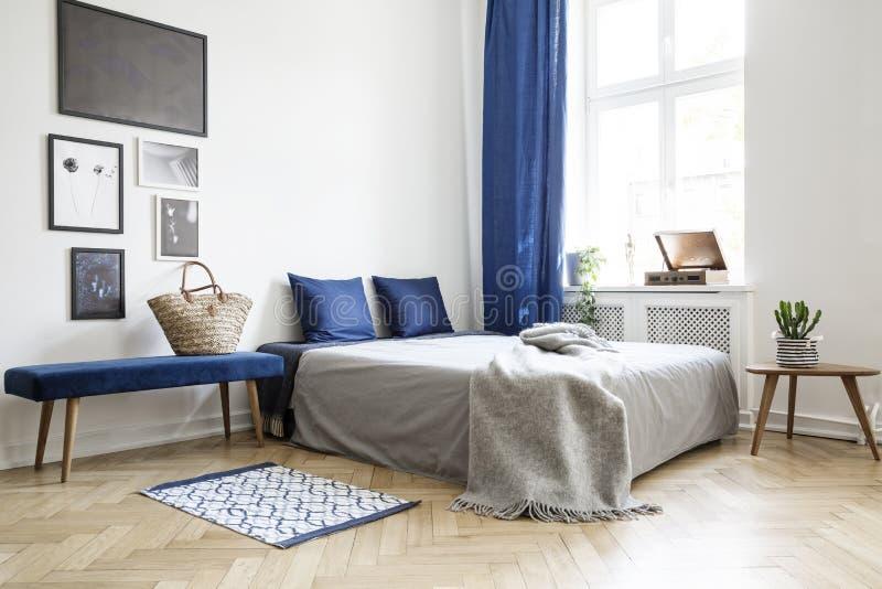 Sypialnia projekt w nowożytnym mieszkaniu Łóżko błękitne poduszki, popielaty duvet i koc obok okno z zmrokiem - obrazy stock