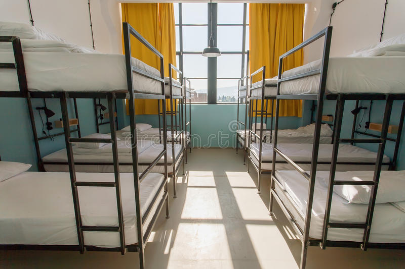 Sypialnia z dużymi okno wśrodku schroniska z wiele łóżkami dla młodych podróżników fotografia royalty free