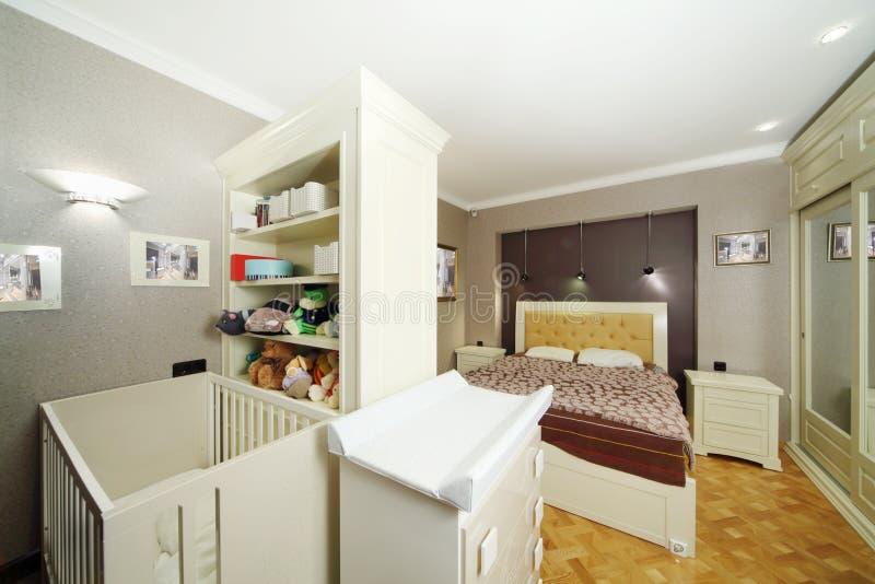 Sypialnia z dwoistym łóżkiem, biały dziecka łóżko polowe fotografia stock