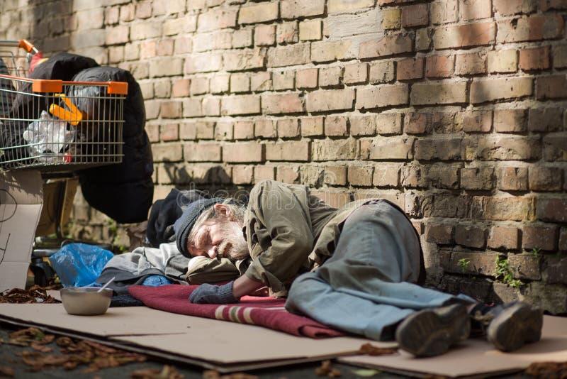 Sypialny bezdomny mężczyzna lying on the beach na kartonie zdjęcia stock
