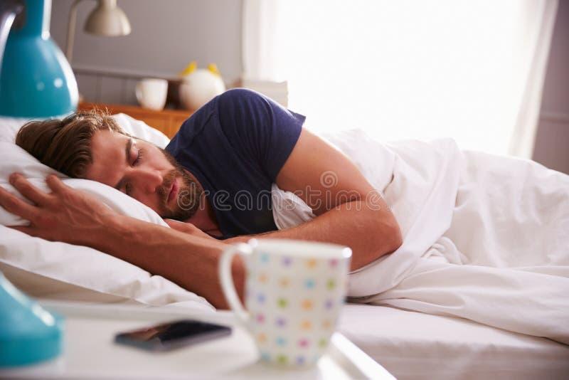 Sypialny mężczyzna Budzi się telefonem komórkowym W sypialni zdjęcia stock