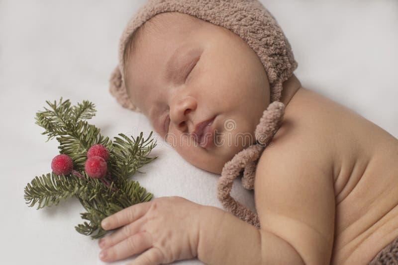 Sypialny nowonarodzony dziecko w śmiesznym kapeluszu trzyma sprig jodła zdjęcie royalty free