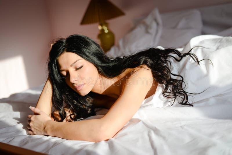 Sypialny piękno: wizerunek pięknej młodej kobiety brunetki seksowna romantyczna dziewczyna relaksuje kłaść na białym łóżku z ocza zdjęcia royalty free