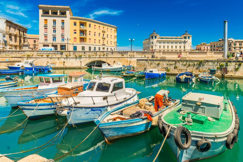 Cityscape of Syracuse with colorful boats, bridge and historical buildings with blue sky in the background. Syracuse - April 2019, Sicily, Italy: Cityscape of stock photos